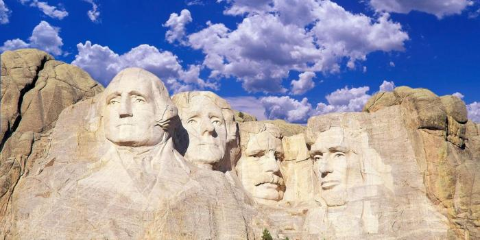 Composite image of Mount Rushmore and blue sky with white clouds