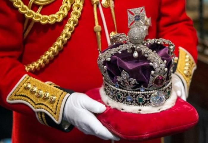 Britain's Queen Elizabeth's crown is carried through the Norman Porch of the Palace of Westminster after the State Opening of Parliament on June 4, 2014 in London