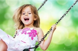 124269562-little-child-blond-girl-having-fun-on-a-swing